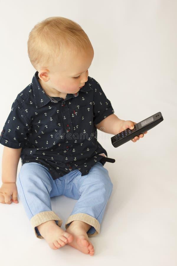 Weinig jongen die op de telefoon op een witte achtergrond spreken royalty-vrije stock afbeelding