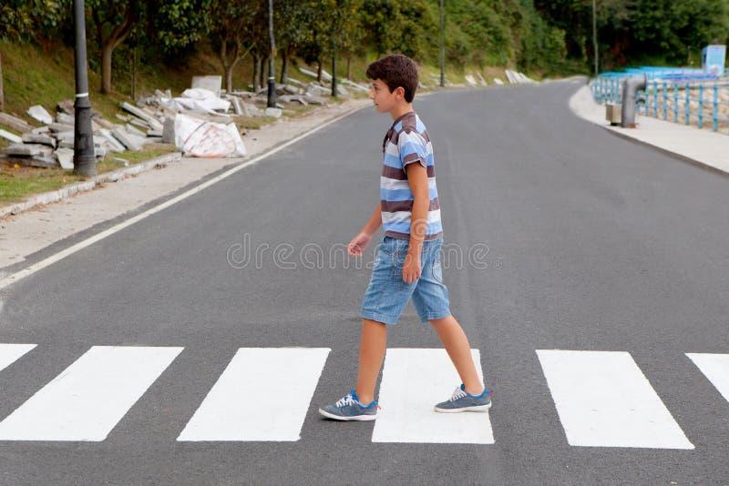Weinig jongen die op de weg kruisen stock afbeelding