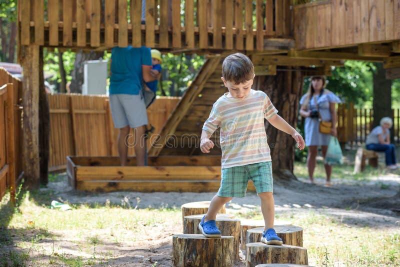 Weinig jongen die op een houten speelplaats in kabelpark beklimmen Warme zonnige de zomerdag van het jong geitjespel in openlucht royalty-vrije stock foto's