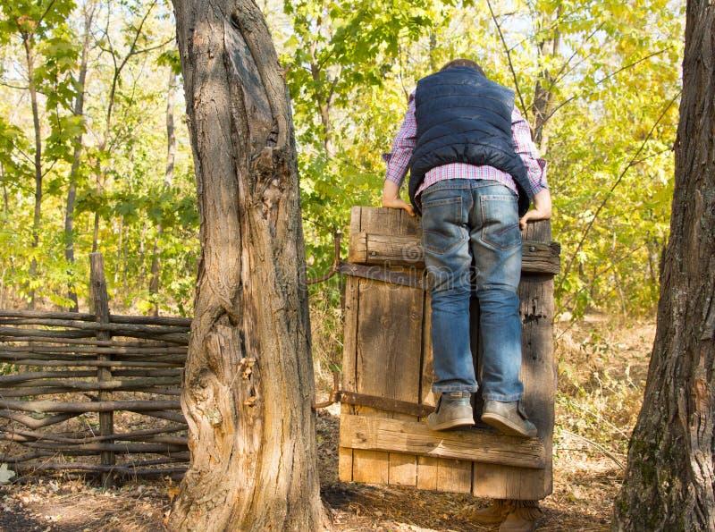 Weinig jongen die op een oude rustieke poort spelen stock afbeelding