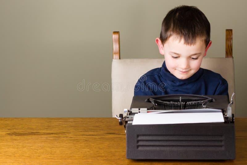 Weinig jongen die op een oude schrijfmachine schrijven royalty-vrije stock fotografie