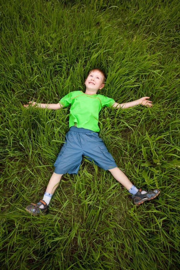 Weinig jongen die op het gras legt stock afbeeldingen