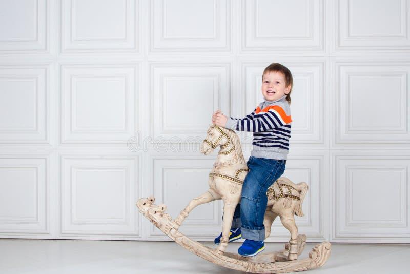 Weinig jongen die op houten paard slingeren grappige drie-jaar-oude jongen in jeans en sweater op witte achtergrond Onbezorgde ki royalty-vrije stock afbeeldingen
