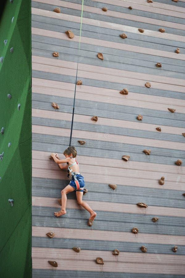 Weinig jongen die op moedig bij speelplaats in openlucht vrije tijd beklimmen stock fotografie