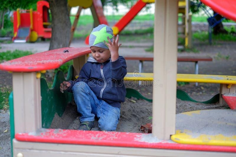 Weinig jongen die op speelplaats in openlucht de herfstpark spelen royalty-vrije stock fotografie