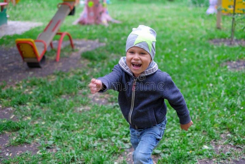 Weinig jongen die op speelplaats in openlucht de herfstpark spelen royalty-vrije stock foto's
