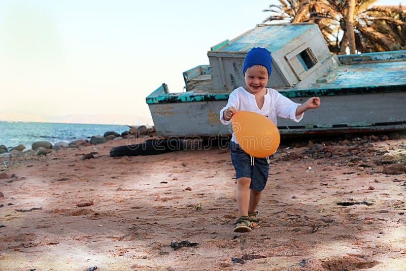 Weinig jongen die op strand lopen royalty-vrije stock afbeeldingen
