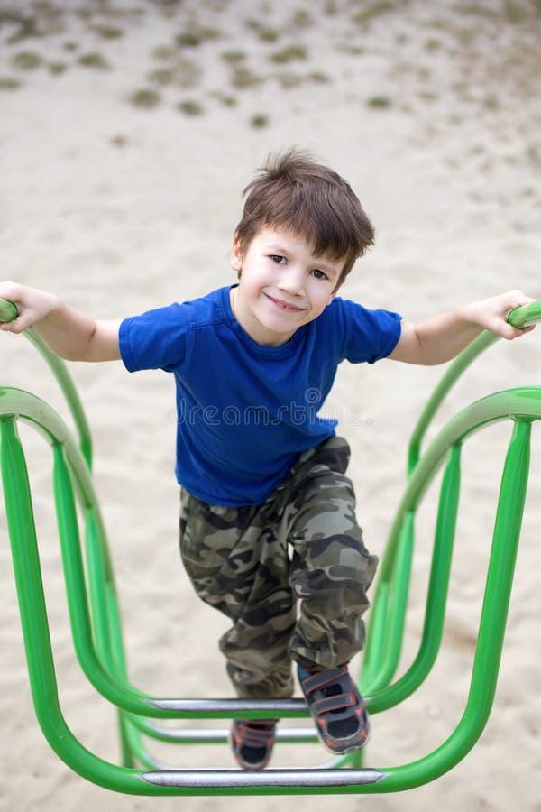Weinig jongen die op wildernisgymnastiek beklimmen royalty-vrije stock foto's