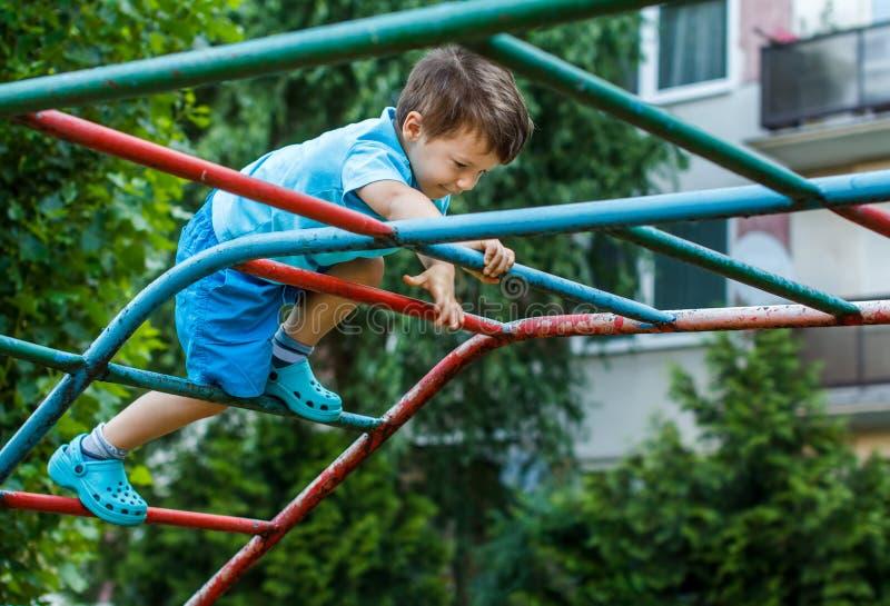 Weinig jongen die op wildernisgymnastiek beklimmen zonder kabel en helm stock foto's