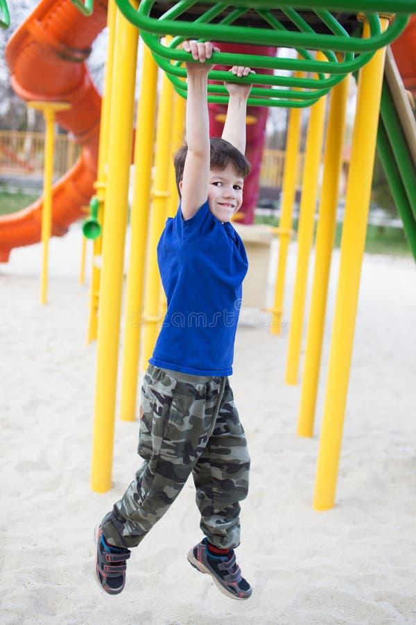 Weinig jongen die op wildernisgymnastiek hangen royalty-vrije stock foto's
