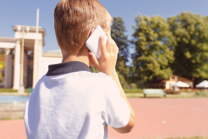 Weinig jongen die per mobiele telefoon spreken stock afbeelding