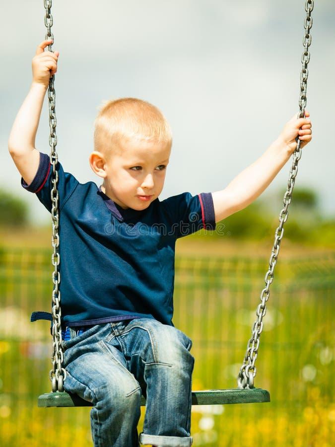 Weinig jongen die pret hebben bij de speelplaats Kindjong geitje het spelen op een schommeling openlucht Gelukkige actieve kinder royalty-vrije stock fotografie