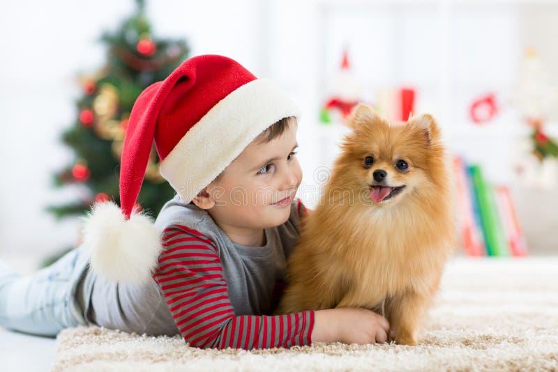 Weinig jongen die puppyhond omhelzen bij Kerstmis, Nieuwe jaarachtergrond royalty-vrije stock foto's