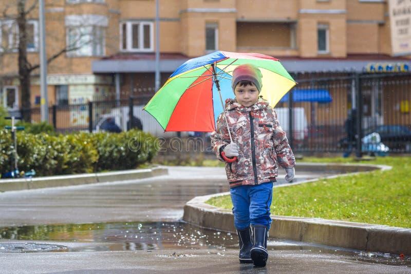 Weinig jongen die in regenachtig de zomerpark spelen Het kind met kleurrijke regenboogparaplu, maakt laag en laarzen springend in royalty-vrije stock afbeeldingen