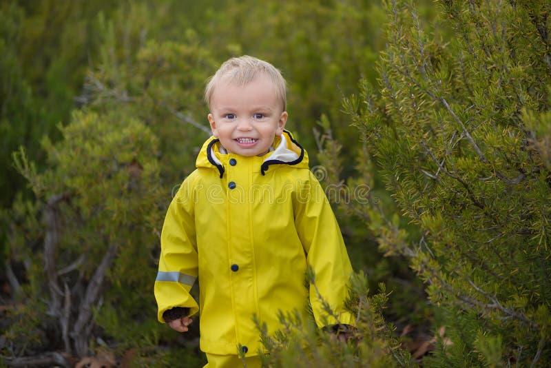 Weinig jongen die in regenachtig de zomerpark spelen Het kind met kleurrijke regenboogparaplu, maakt laag en laarzen waterdicht b stock foto's