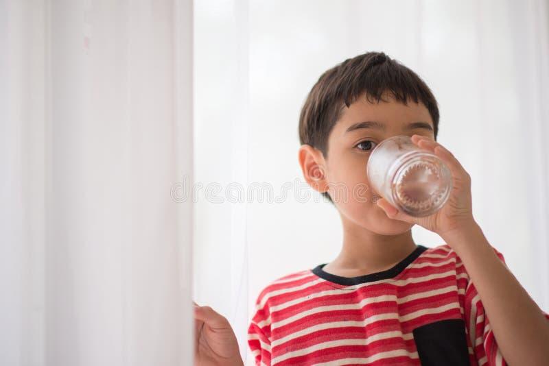 Weinig jongen die schoon water drinken stock fotografie