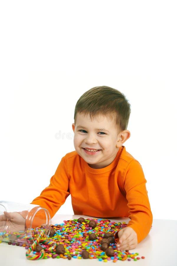 Weinig jongen die snoepjes eet stock afbeelding