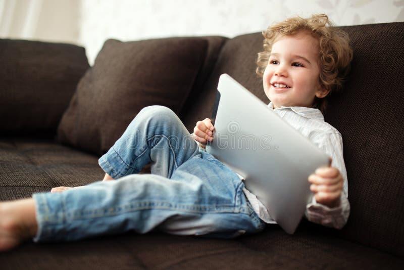 Weinig jongen die tabletcomputer met behulp van stock fotografie