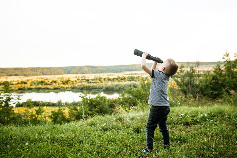 Weinig jongen die telescoopooglens onderzoeken stock foto's