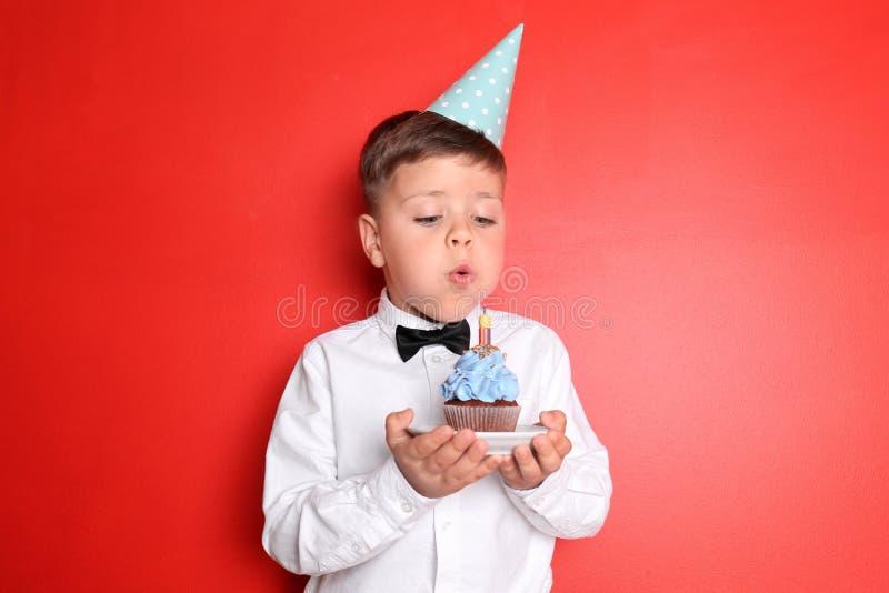Weinig jongen die uit kaars op verjaardag blazen cupcake tegen kleurenachtergrond royalty-vrije stock foto