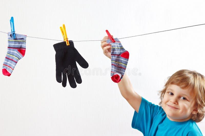Weinig jongen die uw handschoen en sokken hangen royalty-vrije stock foto
