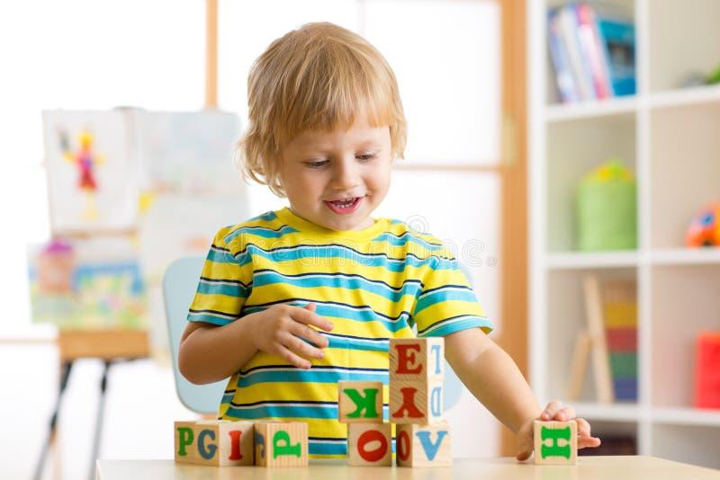 Weinig jongen die van het kleuterkind met stuk speelgoed kubussen spelen en brieven onthouden Vroeg onderwijsconcept royalty-vrije stock afbeeldingen