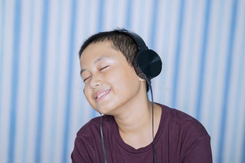Weinig jongen die van muziek in de slaapkamer genieten stock afbeelding