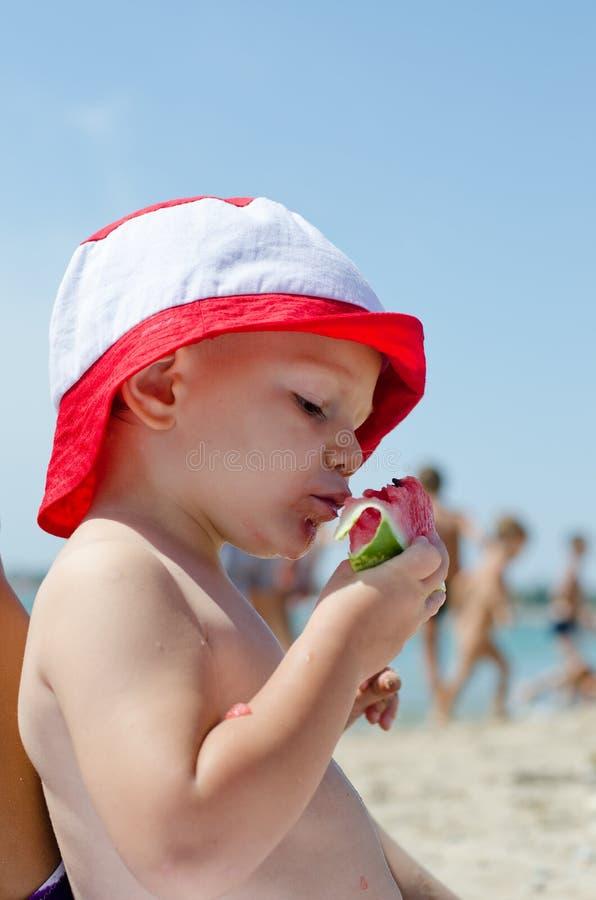 Weinig jongen die watermeloen eten bij royalty-vrije stock afbeelding