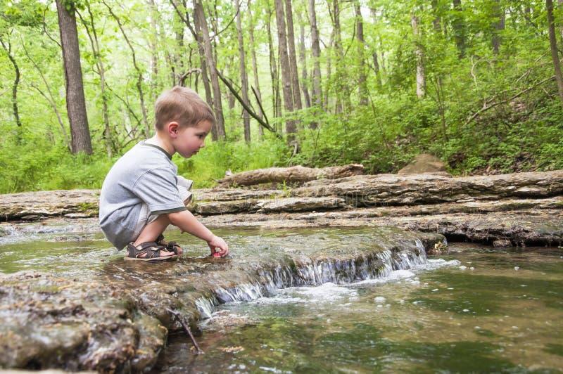 Weinig jongen die in waterval spelen royalty-vrije stock afbeeldingen