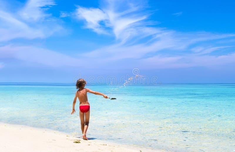 Weinig jongen die in zand op tropisch strand spelen royalty-vrije stock fotografie