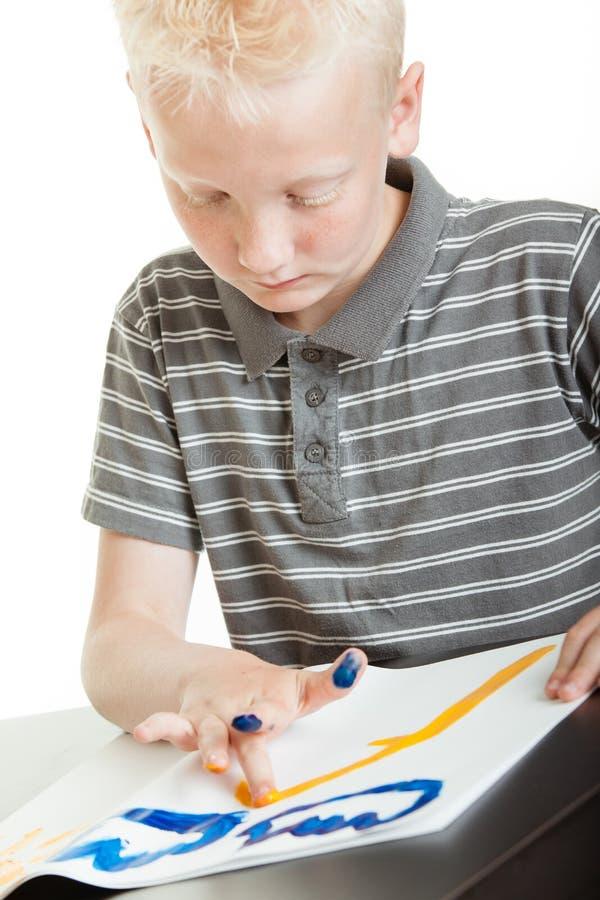 Weinig jongen die zich bij zijn vinger het schilderen concentreren royalty-vrije stock foto's