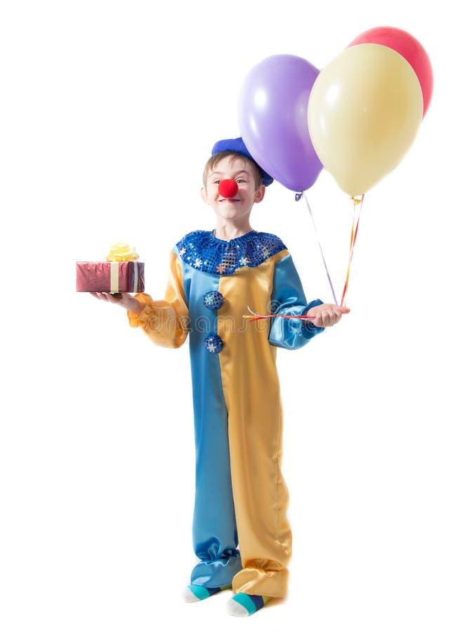 Weinig jongen die zich in een clownkostuum met een rode neus en drie ballons houden en een doos met een boog bevinden royalty-vrije stock foto