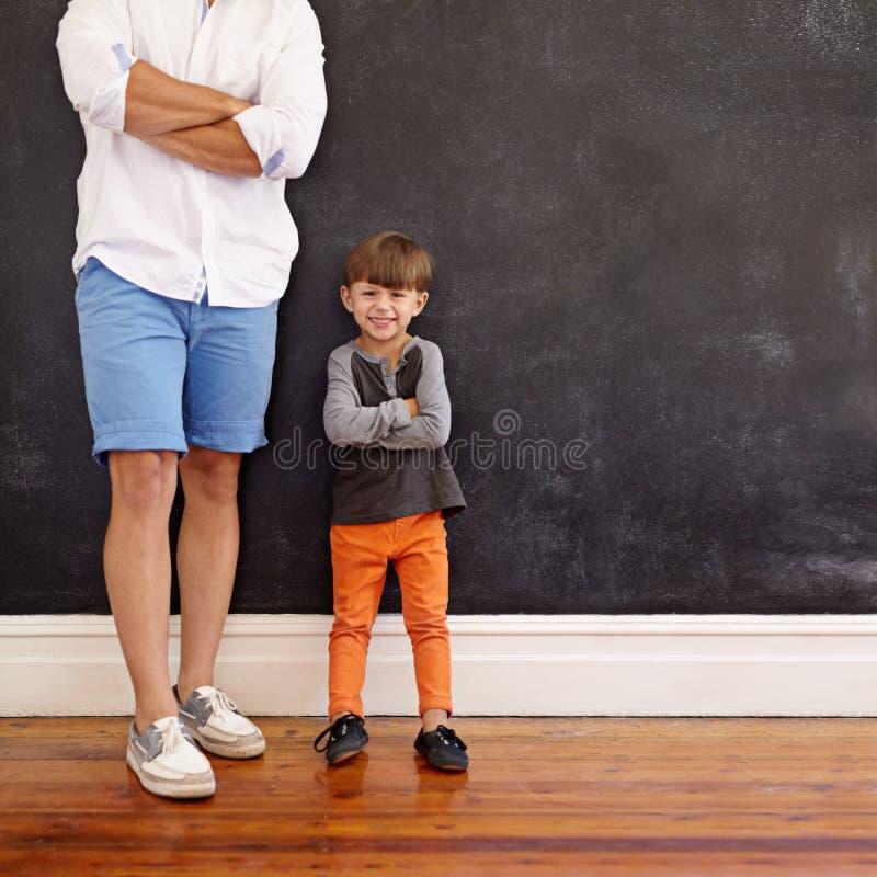 Weinig jongen die zich naast zijn vader het glimlachen bevinden royalty-vrije stock foto