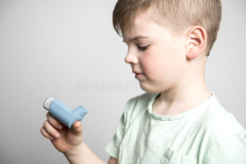 Weinig jongen die zijn astmapomp op studio witte achtergrond gebruiken stock fotografie