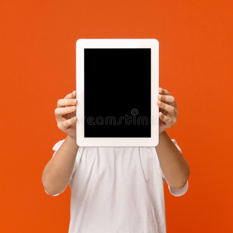 Weinig jongen die zijn gezicht achter digitale tablet verbergen royalty-vrije stock foto