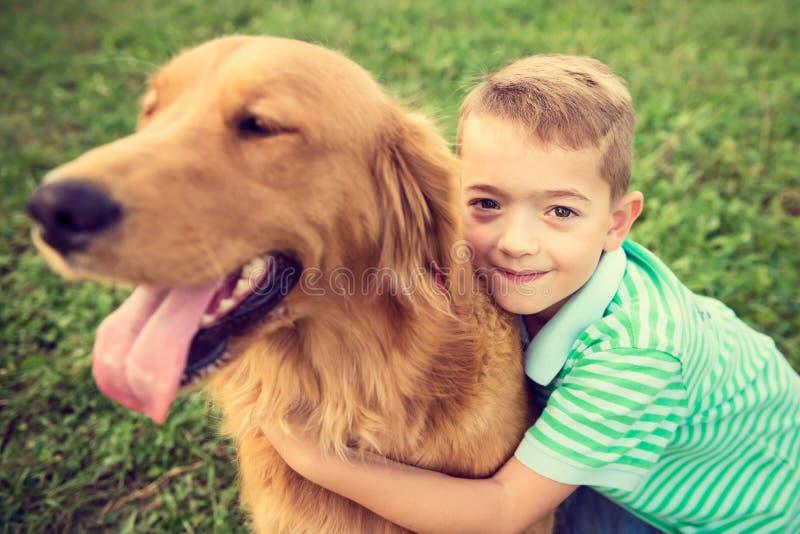 Weinig jongen die zijn hond van het golden retrieverhuisdier koesteren stock afbeelding