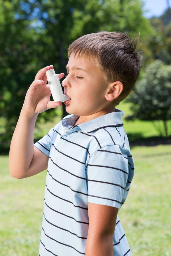 Weinig jongen die zijn inhaleertoestel met behulp van stock foto