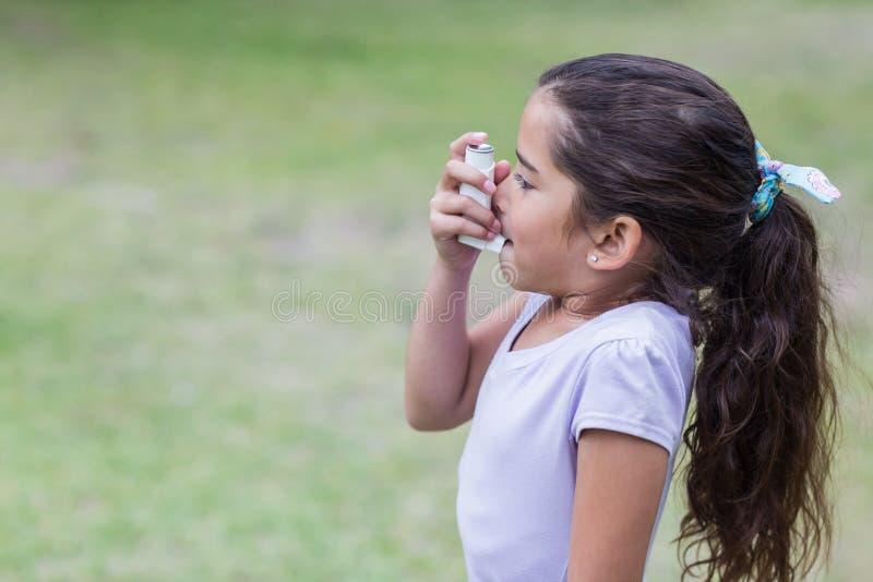 Weinig jongen die zijn inhaleertoestel met behulp van stock afbeelding