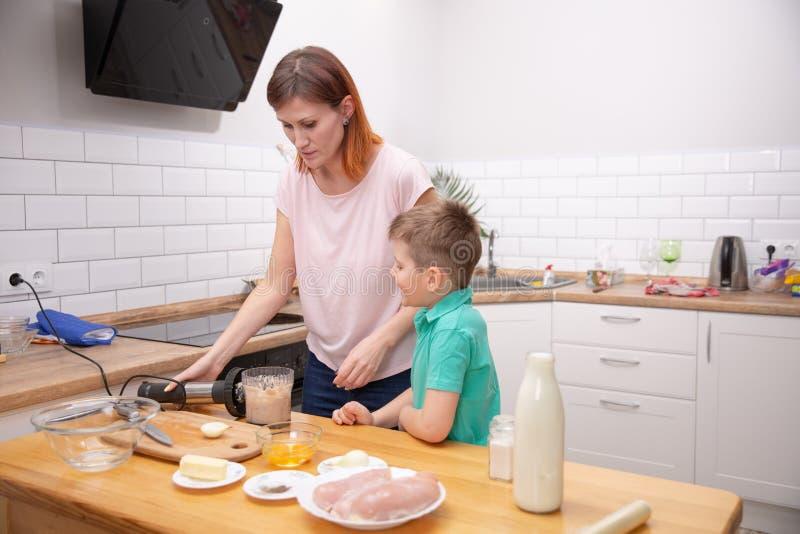 Weinig jongen die zijn moeder met het koken in de keuken helpen stock foto's