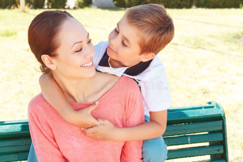 Weinig jongen die zijn moeder omhelzen royalty-vrije stock afbeelding