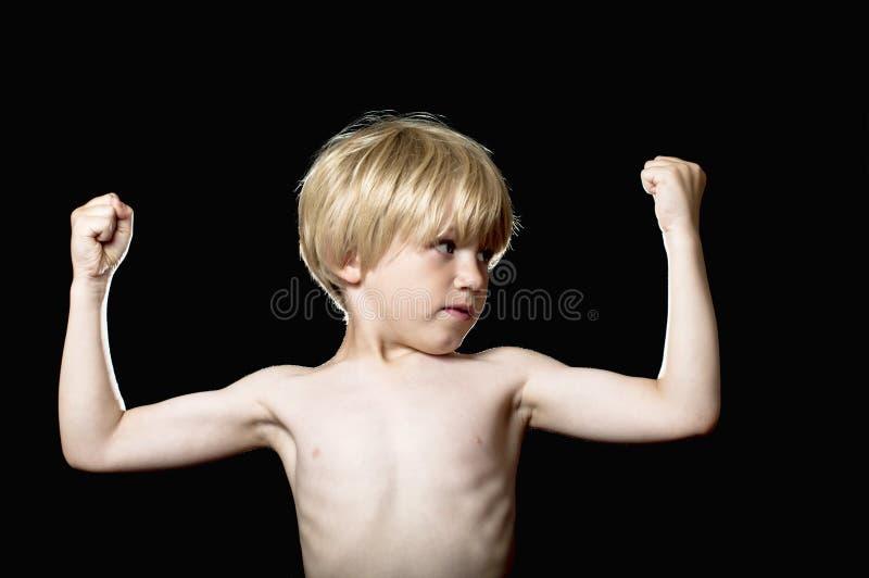 Weinig jongen die zijn spieren buigt stock foto's