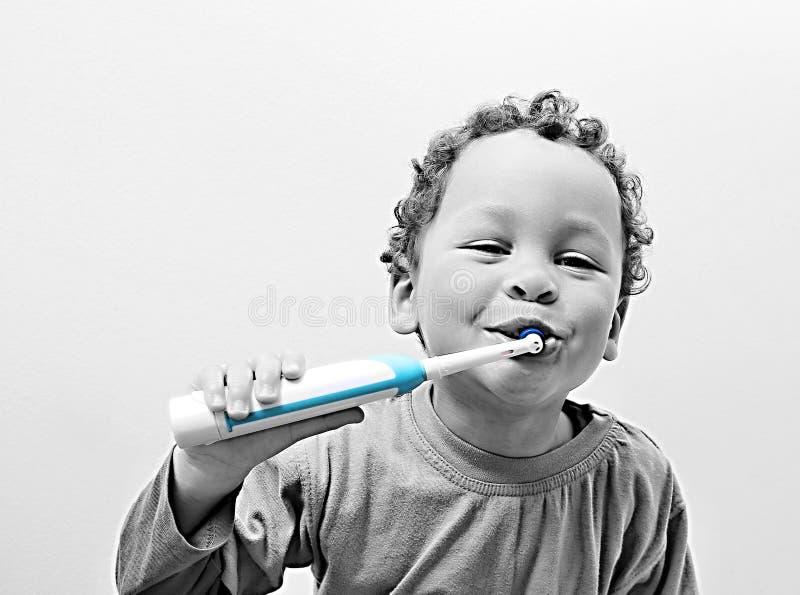 Weinig jongen die zijn tanden met een elektrische tandenborstel borstelen stock afbeelding