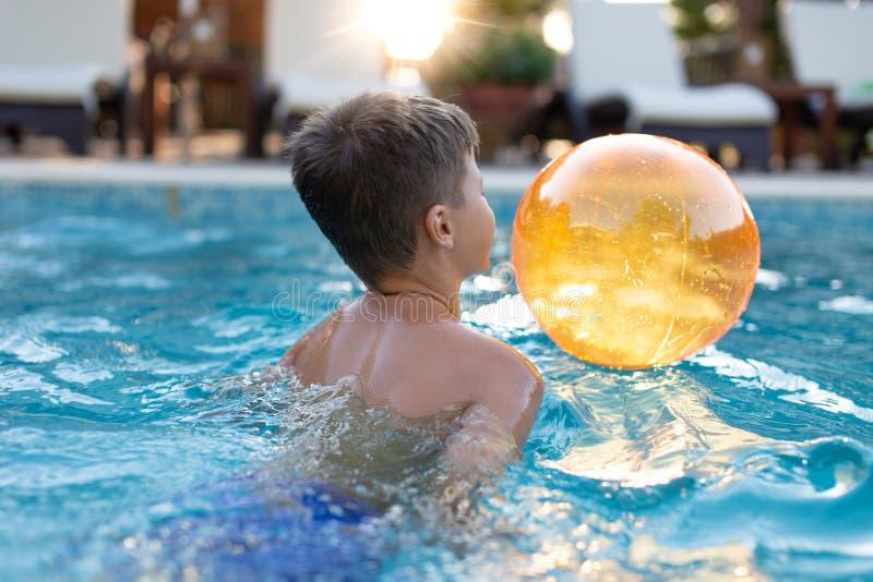Weinig jongen die in zwembad met strandbal spelen stock afbeeldingen