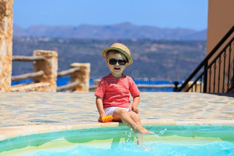 Weinig jongen die in zwembad spelen stock afbeelding