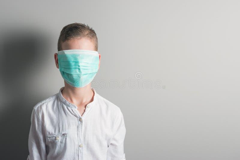 Weinig jongen, een kind in een medisch masker op een heldere achtergrond Het idee van een epidemie, griep, bescherming van ziekte royalty-vrije stock afbeelding