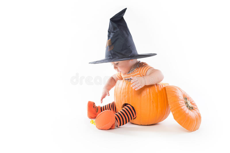 Weinig jongen in een pompoen in heksenhoed die voor suikergoed bereiken stock afbeeldingen