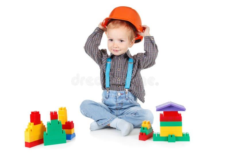 Weinig jongen in een rode bouwbouwvakker op witte achtergrond royalty-vrije stock afbeeldingen