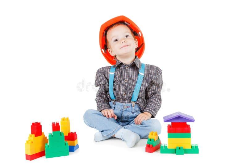 Weinig jongen in een rode bouwbouwvakker op witte achtergrond royalty-vrije stock foto's