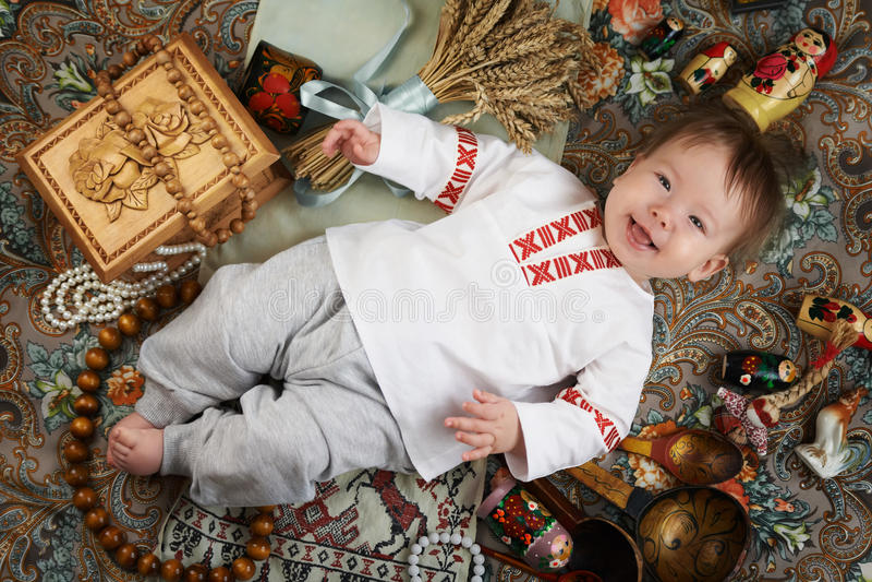 Weinig jongen in een traditioneel Russisch die overhemd door Russische antiquiteiten wordt omringd stock afbeeldingen