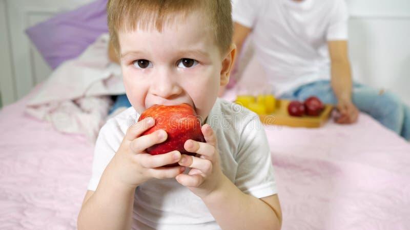 Weinig jongen eet appel in de slaapkamer van de ouder Zijn ouders die op het bed op achtergrond zitten stock afbeeldingen